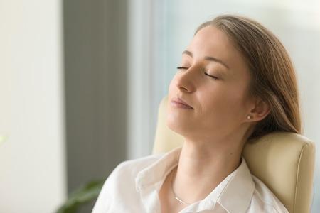 Müde Frau, die auf hinterem Stuhl mit geschlossenen Augen liegt. Die Geschäftsfrau, die tiefe Entspannung tut, trainiert während des harten Arbeitstages. Schönes Mädchen, das über Zukunft im Büro träumt. Kurze Meditation am Arbeitsplatz