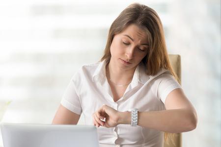 Ernstige onderneemster die aan laptop in bureau en het kijken op polshorloge werken. De vermoeide beambte controleert de resterende tijd tot het einde van de werkdag. Stipte ondernemer wachtende vergadering. Tijd tot deadline Stockfoto