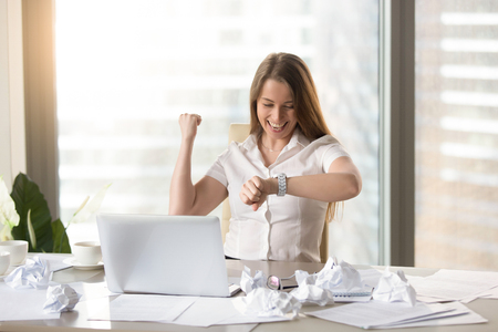 Happy businesswoman at the desk with crumpled papers looking on wristwatches and rejoices work successfully completed in time. Joyful office worker excited because of end a hard day. Cope to deadline