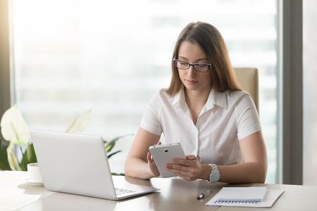 Ernstige onderneemsterzitting bij bureau voor laptop, die computertablet gebruiken. De vrouwelijke beambte controleert e-mail inkomend tekstbericht op phablet. Handige mobiele digitale gadgets voor bedrijfsconcept