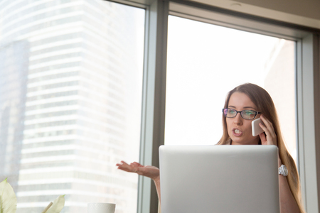 discus: Busy businesswoman arguing on the cellphone in office. Female entrepreneur calling and decides conflict situation at work. Young woman discussing problem by phone. Argumentation in work negotiations Stock Photo