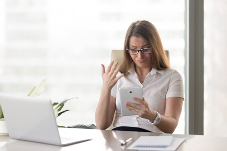 Businesswoman angry because of text or application unstable work on digital tablet. Female entrepreneur disappointed with bad financial results, dissatisfied with negative statements or loan rejection Stock Photo