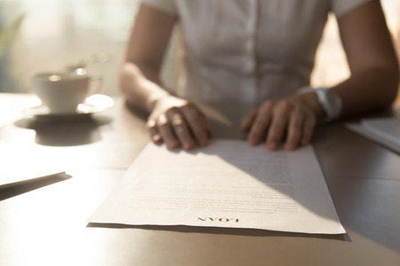 Woman sitting at the desk with loan agreement form. Close up photo of female hands lying on business document. Businesswoman reading  contract terms. Financial adviser analyzing lending conditions Stock Photo