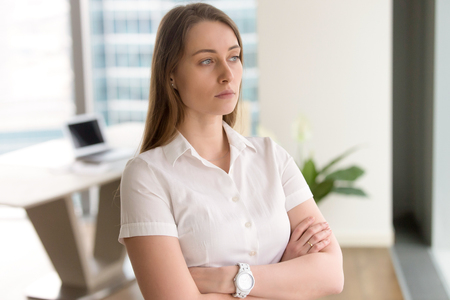 Pensive businesswoman standing with arms crossed in modern office interior. Female entrepreneur looks out of window into the distance, thinking about solution. Female leader concept