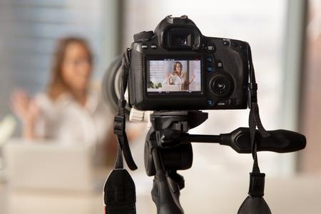 Sluit omhoog beeld van camera op driepoot met glimlachende vrouw op het achterscherm en vage scène op achtergrond. Video opnemen op moderne DSLR-camera. Persoonlijk videoblog sociaal netwerk concept Stockfoto