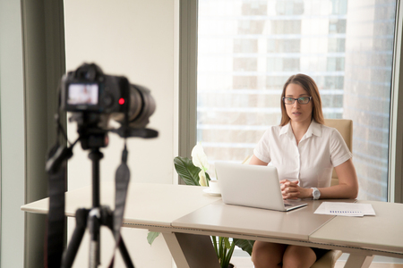 Confident businesswoman sitting at desk in front of laptop and looking at camera on tripod that records video. Female blogger makes footage for social networks. Woman recording videolog at workplace. Stock Photo