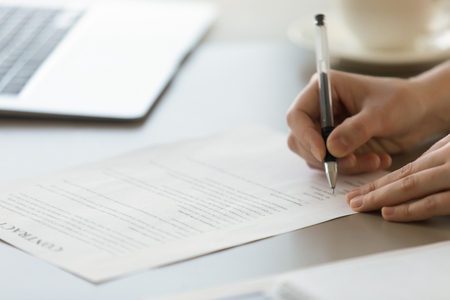 accepts: Close up photo of womans hands signs contract. Businesswoman puts signature to partnership agreement concept. Female entrepreneur accepts conditions of deal. Working with business documents in office