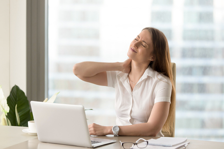 Businesswoman feeling pain in neck after sitting at the table with laptop. Tired female suffering of office syndrome because of long hours computer work. Pretty girl massaging her tense neck muscles Stock Photo