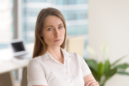 Young serious woman standing in modern office interior with arms crossed. Successful businesswoman ready for challenges in business. Confidence in own strengths, leadership skills concept. Head shot