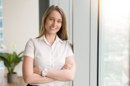 Head shot portrait of smiling attractive young woman with arms crossed looking at camera. Successful positive entrepreneur posing near window. Happy businesswoman works at office, feeling optimistic