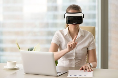 Businesswoman interacts with virtual reality in VR headset. Girl in light office interior wearing virtual glasses and pointing at the air. Working with documents and projects in digital simulation Stock Photo