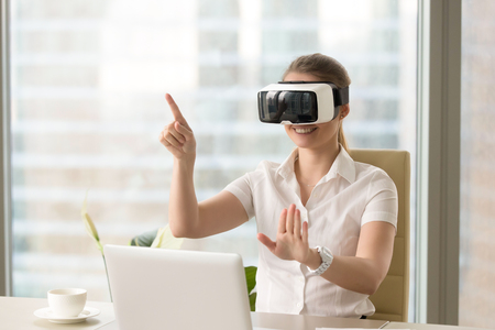 Enjoyed young woman pointing at the air with virtual reality glasses on head. Girl sitting at office table with VR headset and using gestures. Innovative gadget for business 3d visualizations Stock Photo
