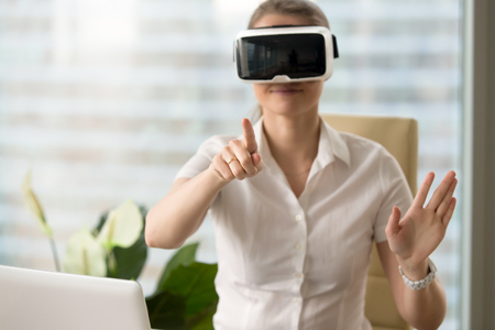 Woman in VR headset touching objects in virtual reality. Girl sitting in armchair at the desk and interacting with 3d visualization. Modern IT product test on digital simulator concept Stock Photo