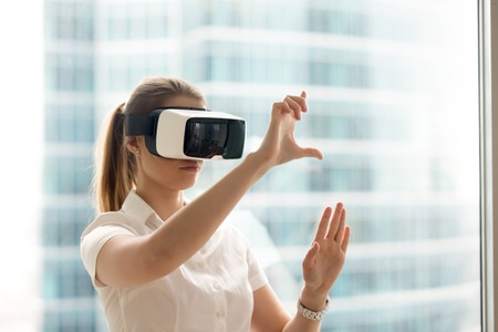 interacts: Beautiful girl using virtual reality glasses near bright window with skyscraper view outside. Business woman wearing VR goggles and interacts with cyberspace using swipe and stretching gestures Stock Photo