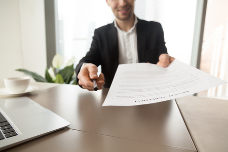Realtor reaching out pen and rental agreement to clients. Real estate consultant sitting at desk in office and offers to read and sign contract document. Readiness to make a deal, rent new dwelling Stockfoto