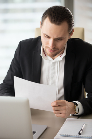 businessman pondering documents: Businessman sitting at desk in front of laptop and looking at document in hands. Male entrepreneur reading correspondence, analyzing company stats or contract. Recruitment manager examines resume Stock Photo