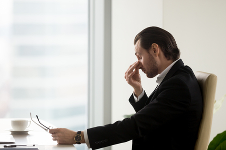 Tired businessman at desk holding eyeglasses in hand and massaging nose bridge. Man feels fatigue in eyes after hard work, discomfort because of long wearing glasses. Eye strain, eyesight problems