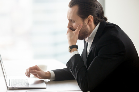 Businessman yawning while working on computer at workplace. Male entrepreneur suffering from lack of sleep, chronic fatigue and drowsiness at desk with laptop. Boring routine, monotonous office work Stock Photo