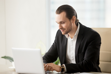 Businessman typing on laptop at desk in office. Office worker discusses with colleagues company policy in chat. Entrepreneur conducts negotiations online, searching new ways of development in Internet
