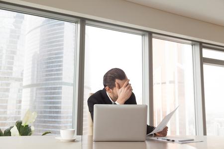悲しい起業家オフィスの机に座って手に悪い決算、頭を心配します。株式、損失、小さな利益は、否定的な年次レポートの統計情報の流動性に分類
