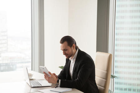 Entrepreneur using digital tablet while sitting at desk in office. Executive manager browsing online with phablet, watching video online. Businessman monitors market, takes part in internet conference