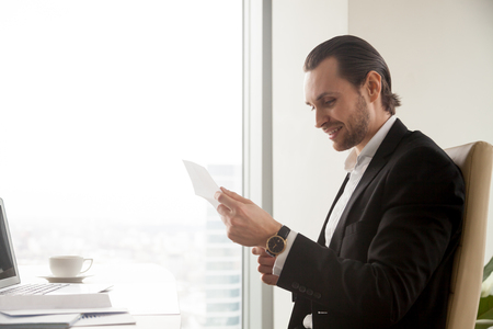 Happy businessman reading document at desk in office. Young guy entrepreneur examines notice, reading letter with good news. Manager satisfied with conditions of contract, receives bank loan approving Stock Photo