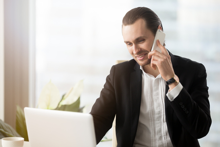 Young entrepreneur answers the call at workplace. Financial adviser consults clients by phone. Head of company calling supplier while searching best offer on laptop online. Employee workflow concept