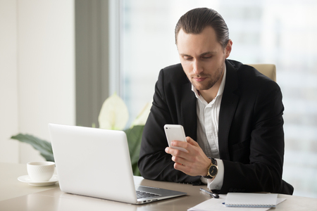 Successful businessman dials number on cellphone at desk with laptop. Attractive entrepreneur using mobile app on phone, guy reading message or news, checks schedule of business meetings at workplace