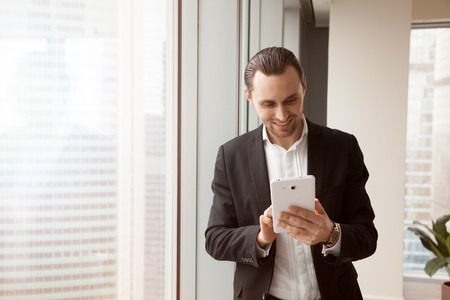 Joyful businessman using computer tablet for managing tasks, organizing meeting schedule, conversation with colleagues. Happy smiling entrepreneur browsing online with phablet, works with mobile app Stock Photo