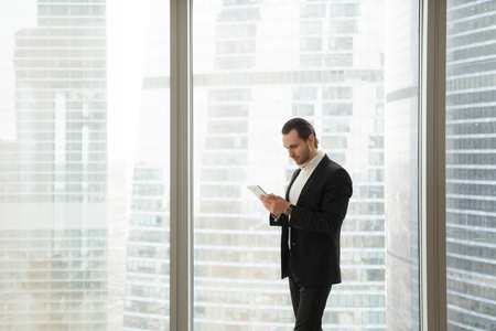 Businessman working on tablet while standing near large window in office. Entrepreneur reading news or messages in internet, accounting or banking online, monitors stock prices, planning daily work