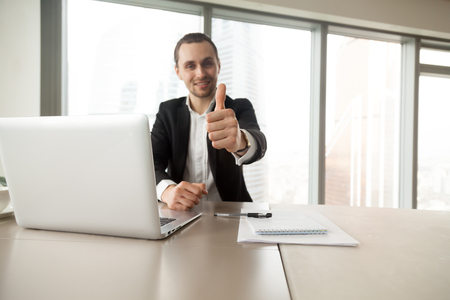 Confident businessman showing thumbs up gesture at desk in office. Entrepreneur satisfied with work results. CEO supports good decision, recommends proven solution. Company leader like successful idea