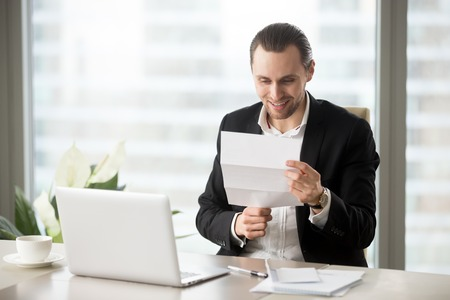 pay raise: Smiling businessman looking at document in hands while sitting at desk with laptop. Happy entrepreneur reading letter with good news. Office worker guy gets pay raise, premium bonus from his employer Stock Photo