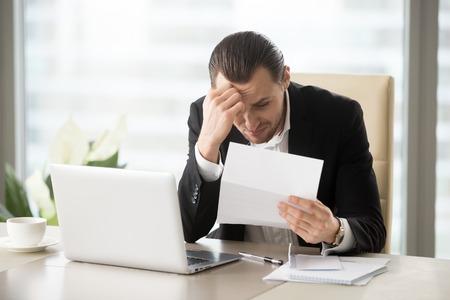 Beklemtoonde zakenman van streek wegens bankbrief met waarschuwingen over leningsschuld. Verdrietig man maakt zich zorgen over financiële problemen. Beambtezitting die bij bureau na wordt geschokt ontvangt kennisgeving van ontslag
