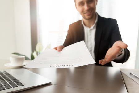 Company lawyer or representative offers to read and sign a contract. Smiling guy at desk reaching out contract to a partner. Successful entrepreneur promising good deal with beneficial terms. Close up Stock Photo