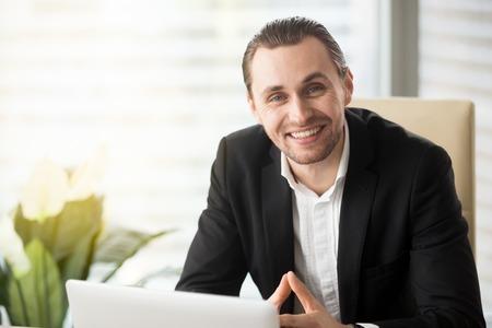 幸せな青年実業家のオフィスで作業机に座って大きく見開いた友好的な笑みを浮かべてカメラで探して。よいオフィスの一日を楽しんで、結果に満 写真素材
