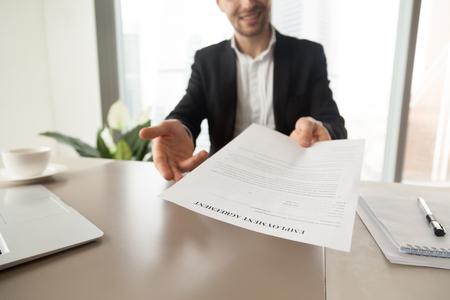 고용 계약서를 시트 밖으로 도달하는 모집 관리자. 스마일 CEO는 작업 조건을 읽고 확인하고, 문서에 서명하도록 초대합니다. 새로운 직업을 얻고, 협상