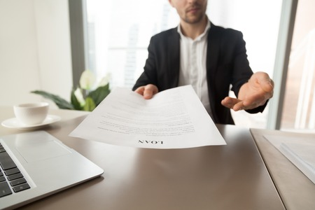 Bank employee offers to read and check loan agreement form. Financial consultant advises to take loan on business purpose, new house buying. Company partner invites to sign mortgage contract. Close up Stock Photo