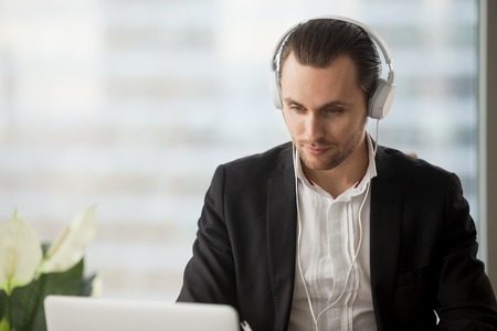 live stream listening: Young man in headphones listening music while working on laptop in office, watching video, live stream, webinar, enjoys web content. Entrepreneur takes part in online meeting or business negotiations Stock Photo