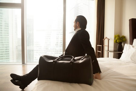 Businessman with luggage sitting on bed in hotel room interior enjoys city view in window. Entrepreneur resting after flight in foreign country on work meeting with partners. Business tourism concept