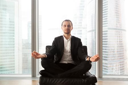 蓮華座の柔らかい椅子に座っている青年実業家。胡坐とソファの瞑想ビジネス スーツの穏やかな男は。メンタルヘルス、ストレス リリーフのための 写真素材