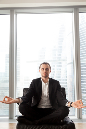 Businessman meditating on coach with crossed legs. Entrepreneur relaxing in lotus position, concentrates on positive thoughts, struggling with stress. Man doing yoga exercises near window, copy space Banco de Imagens - 81601572