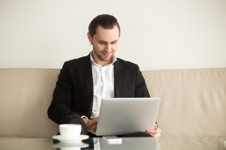 Entrepreneur on vacation controls business, checks financial indexes in Internet. Businessman on sofa with laptop remotely managed his ecommerce company. Young man communicates with colleagues online 版權商用圖片