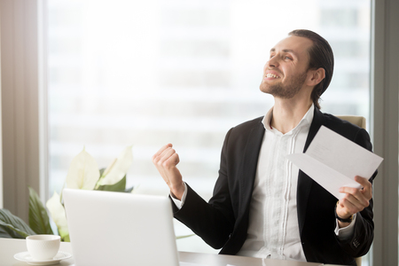 Successful businessman saying yes with document in hand. Happy excited entrepreneur celebrates victory, achievements in work. Manager glad to get important contract, promotion, feeling great success Stock Photo