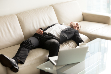 Tired businessman lying relaxed on sofa. Man fall asleep on couch in office when stayed at work till late. Entrepreneur takes short break, recovery sleep after too much hard work at project on laptop Stock Photo