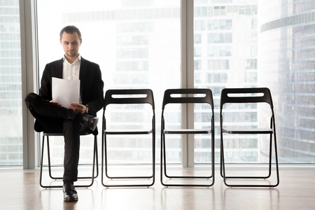 Confident job applicant reads resume while sitting on chair in row in office and waiting his turn on interview. Young guy wearing suit prepares for recruitment meeting with employer in waiting room Foto de archivo