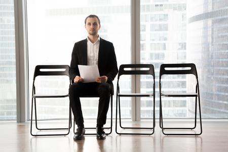 사무실에서의 자에 앉아 젊은 남성 후보자 이력서에 손. 구직 신청자는 고용주와 이야기하기 전에 걱정하고, 대기실에서 인터뷰 할 때 기다리는 동안  스톡 콘텐츠