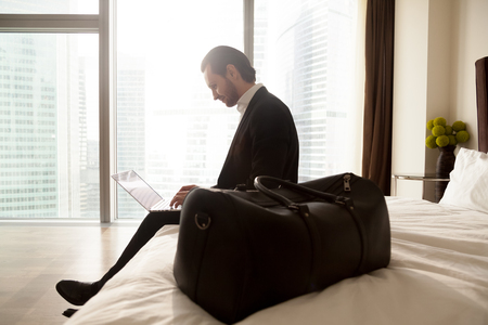 executive apartment: Business tourist communicates online with colleagues from hotel. Businessman with luggage working on laptop sitting on bed in apartments. Entrepreneur orders travel tour or airline tickets in Internet