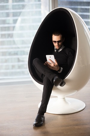 Young attractive man in stylish wear and sunglasses working on tablet computer while sitting in futuristic egg chair. Successful businessman managing company or shopping online, entertains in Internet