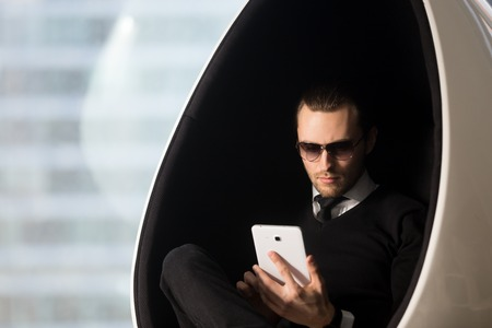 Young attractive model guy in sunglasses and stylish formal wear sitting in comfortable egg chair and looking on tablet computer in his hands. Businessman reads e-book, revising meetings schedule Stock Photo
