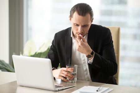 사업가 물 한잔 사무실에서 직장 책상에서 흰색 라운드 알 약을 걸립니다. 회사원 직장에서 마약을 마시는입니다. 젊은 기업가 진통제, 효율 회복을위 스톡 콘텐츠